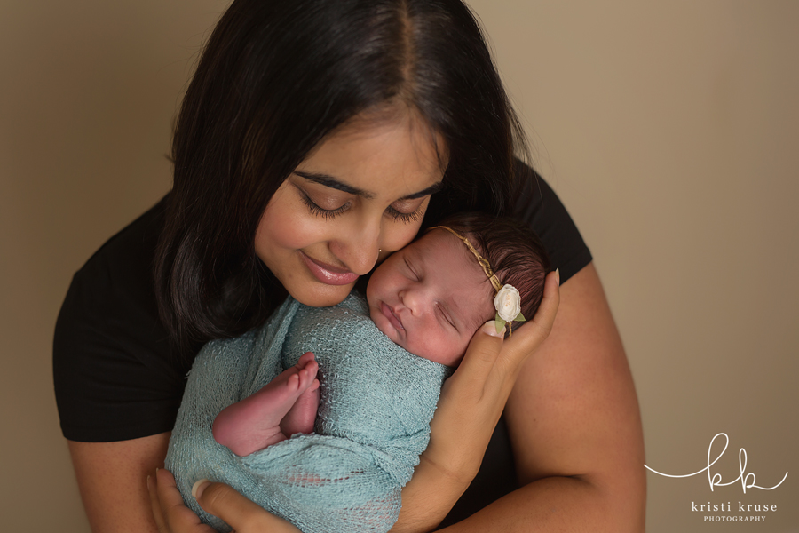 Mom in black shirt holding newborn baby wrapped in blue blanket up close to her cheek