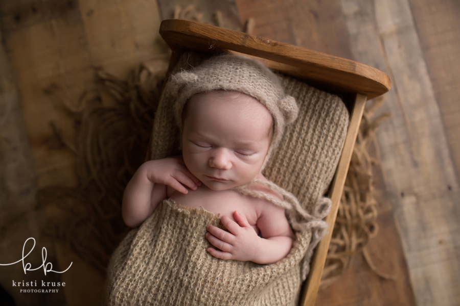 Baby boy in brown bear hat and blanket laying in tiny wooden bed