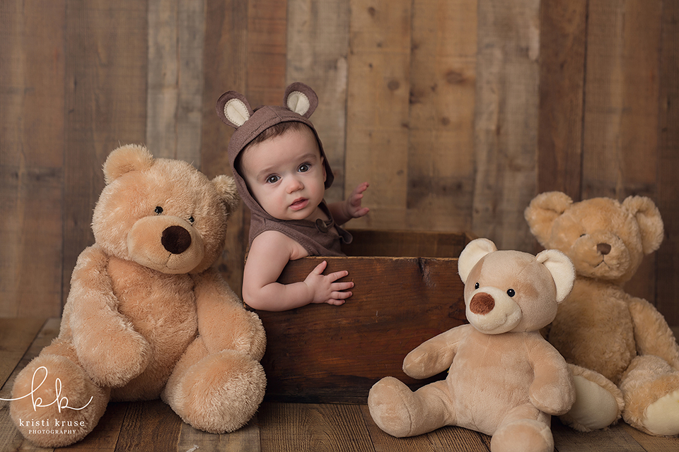 6 month baby boy sitting in brown crate wearing bear outfit surrounded by teddy bears