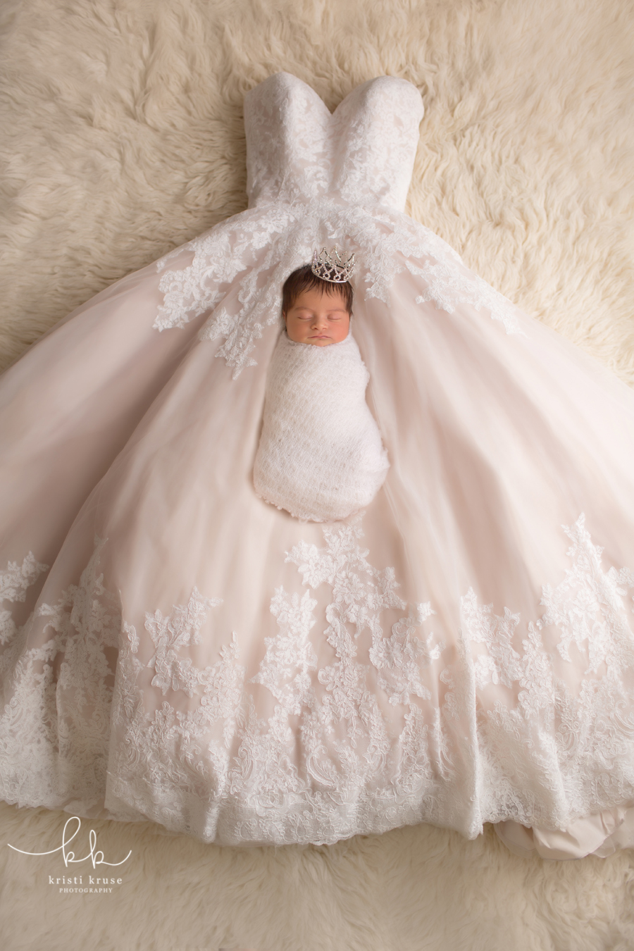 Baby girl wrapped in white swaddle and wearing crown laying on mom's wedding dress