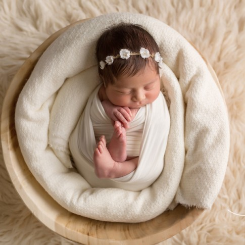 newborn baby girl wrapped in white swaddle laying in wooden bowl on