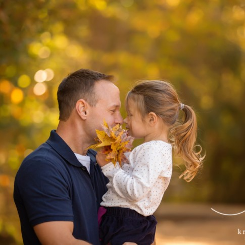 Father in blue shirt holding and giving an eskimo kiss to his 3 year old daughter who is wearing white shirt and blue skirt