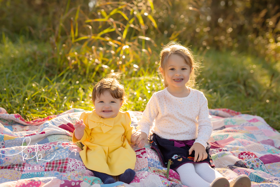 6 month old girl in yellow dress with 3 year old sister with white shirt and blue skirt sitting on patchwork quilt