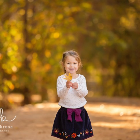 3 year old girl with ponytail wearing white shirt and blue skirt holding a leaf on a wooden trail