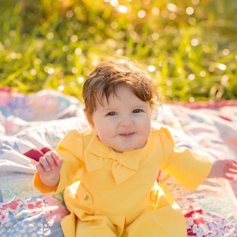 6 month old baby girl in yellow dress sitting on patchwork quilt in tall sunlit grass