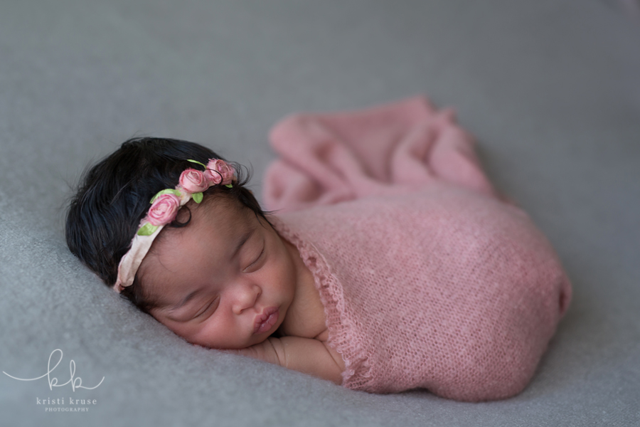 newborn baby girl wrapped in pink swaddle lying on gray blanket