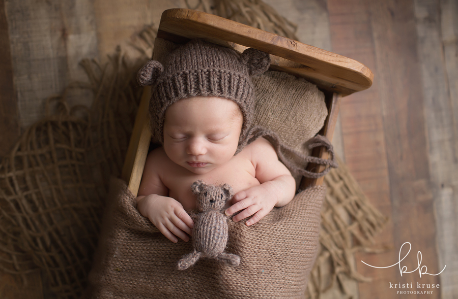 baby boy laying in tiny wooden bed wearing brown knit bear hat holding brown knit bear