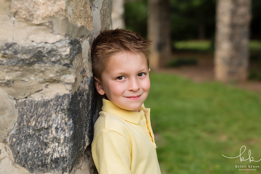 5 year old boy leaning against stone wall looking at camera