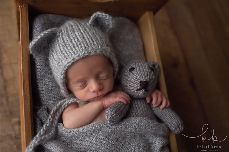 Newborn baby boy in wooden bed wearing gray knit teddy bear hat holding matching teddy bear.