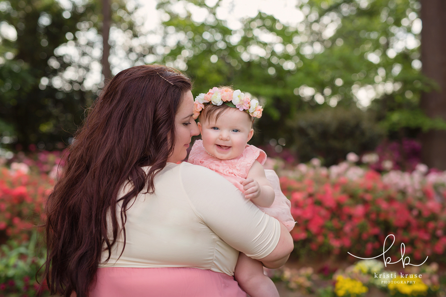 Mom and 6 month old daughter standing in azalea garden surrounding by pink flowers