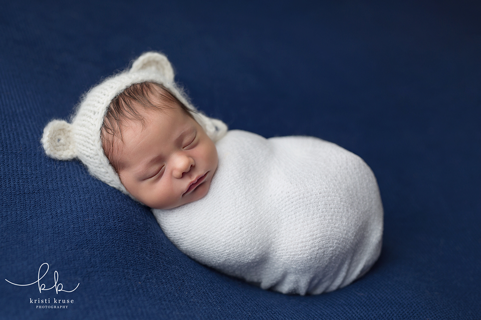 newborn baby boy wrapped in white with white bear hat laying on navy blue blanket