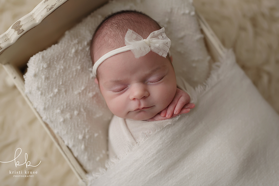 Baby girl laying in cream cradle with cream bow