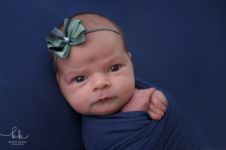 Baby girl laying on navy blanket with blue bow looking at camera