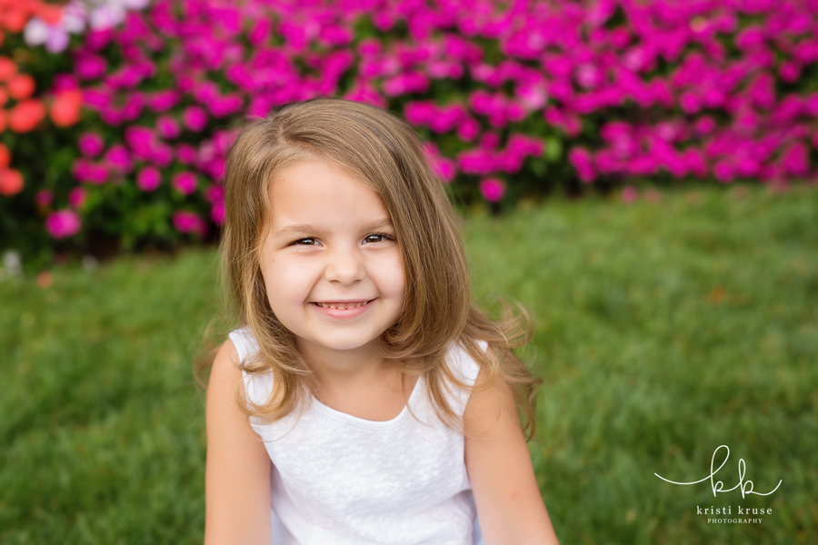 4 year old girl in white dress in front of purple flowers