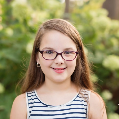 9 year old girl with long brown hair and glasses in front of hydrangea bush