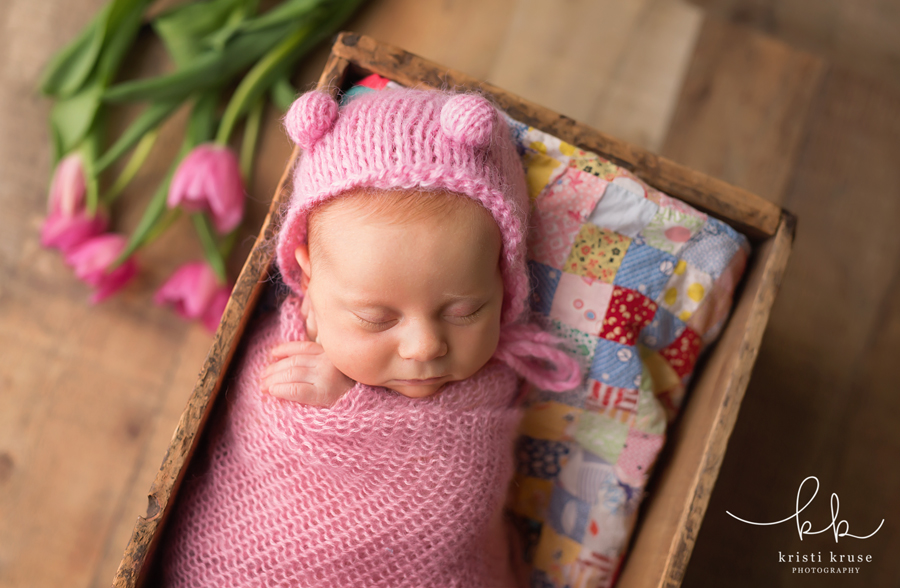Baby girl wrapped in pink with pink bear hat laying on quilt