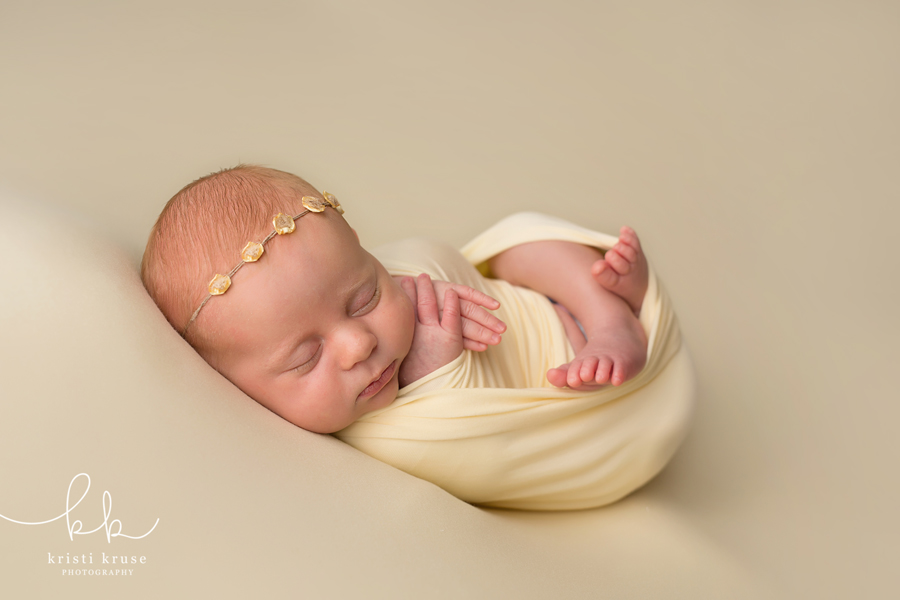 Baby girl swaddled in yellow on yellow blanket sleeping