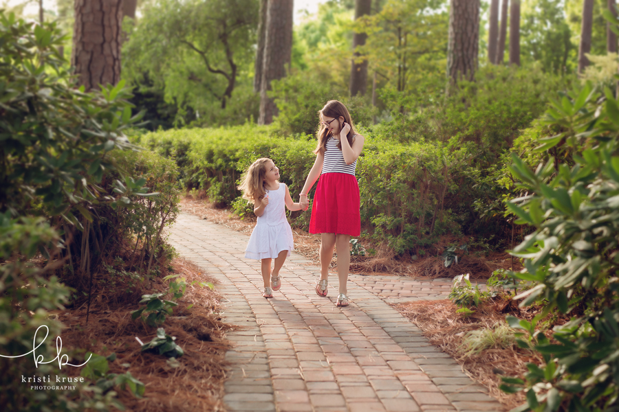 Two sisters walking hand in hand through garden
