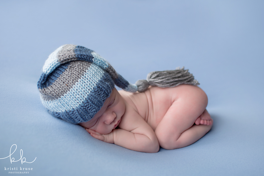 Baby boy lying on blue blanket with striped sleepy cap on