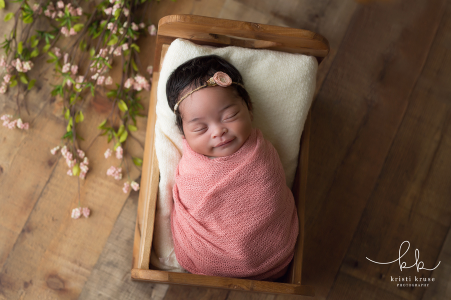 newborn girl wrapped in pink swaddle lying in small bed with flowers