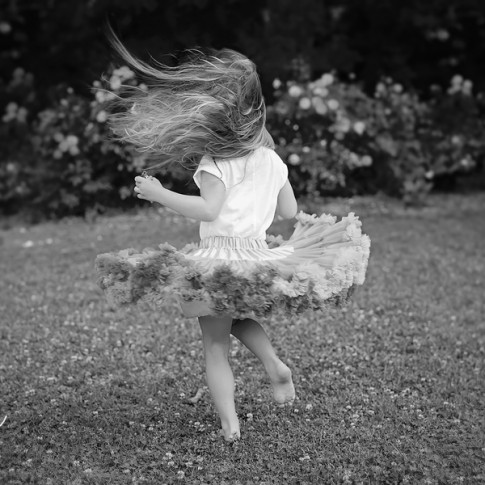 3 year old girl wearing tutu twirling in the grass