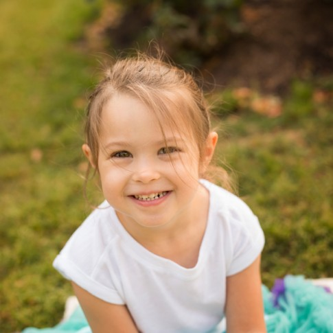 Close up of 3 year old girl wearing white shirt and blue tutu