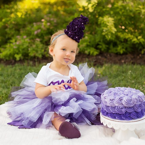 1 year old girl wearing purple tutu with matching hat and onesie with purple birthday cake