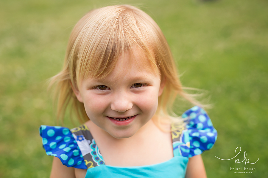 close up of blonde hair 3 year old girl smiling at camera