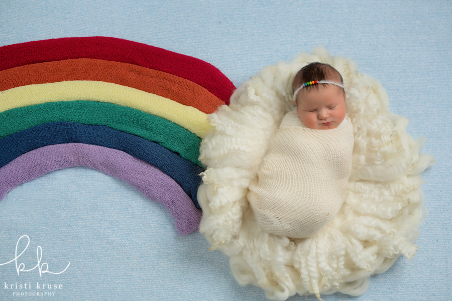 Baby girl in cloud of white fluff with rainbow