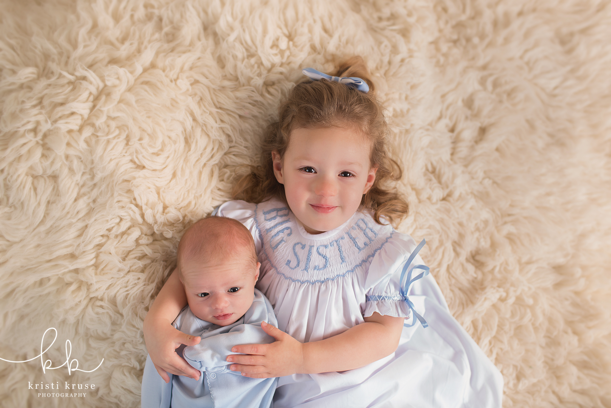 newborn baby boy dressed in blue laying next to 2 year old sister wearing big sister dress