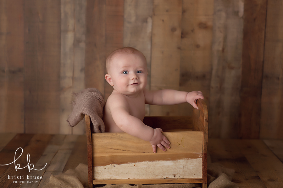 6 month old baby boy sitting in wooden prop bed