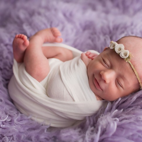 newborn baby girl smiling while laying on a purple flokati