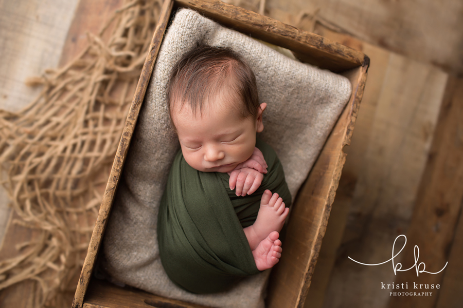 baby boy wrapped in olive swaddle laying in wooden crate with gray blanket