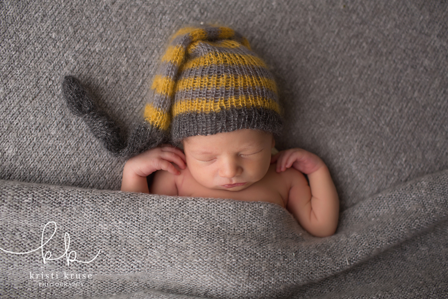 newborn baby lying on gray blanket with striped knit hat