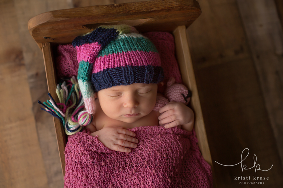 Newborn baby girl in striped knit tassel hat laying in wooden prop bed with tiny teddy bear