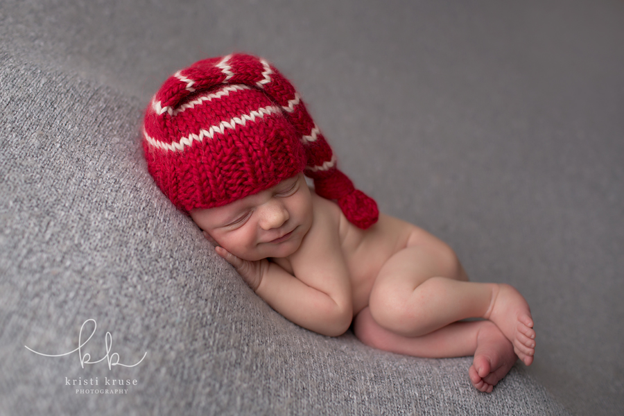 Smiling newborn baby boy laying on gray blanket with red and white striped knit cap.