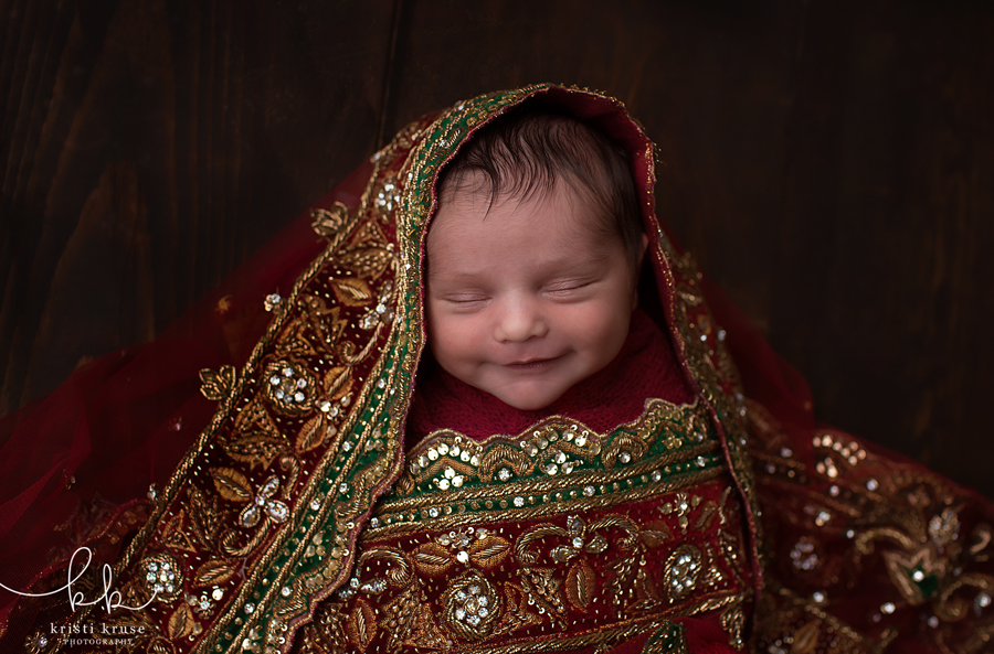 newborn baby girl wrapped in indian wedding sari with big smile