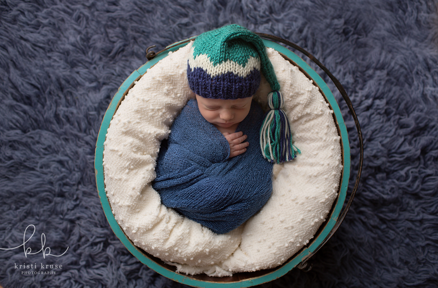 Newborn baby boy wrapped in blue swaddle with green/blue/white striped cap in green bucket on blue rug