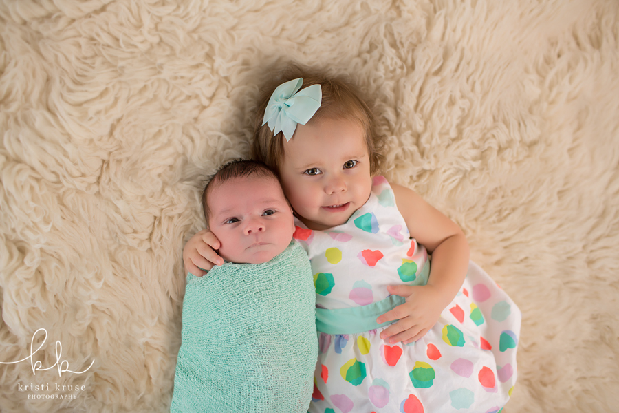2 year old sister in polka dot dress laying next to her newborn brother wrapped in a green swaddle