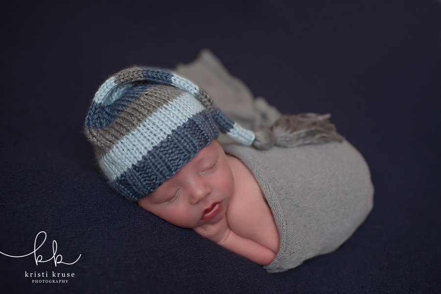 Newborn baby boy wrapped in gray swaddle with striped knit hat on navy blanket