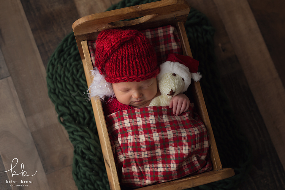 newborn boy with santa hat laying in small bed with teddy bear and plaid blanket