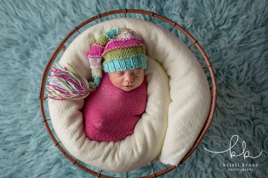 newborn baby girl swaddles in basket