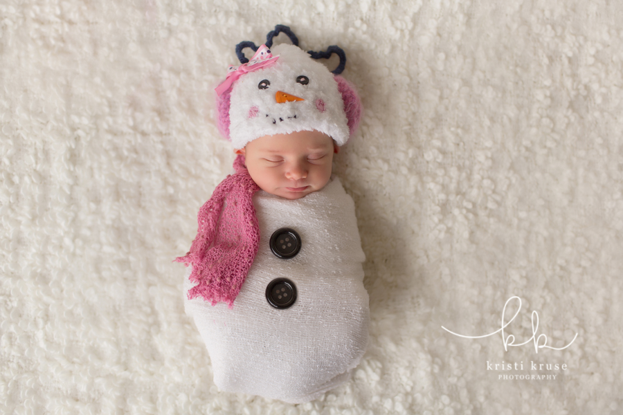 Newborn baby girl with snowman knit hat with pink earmuffs and pink scarf swaddled in white blanket with black buttons