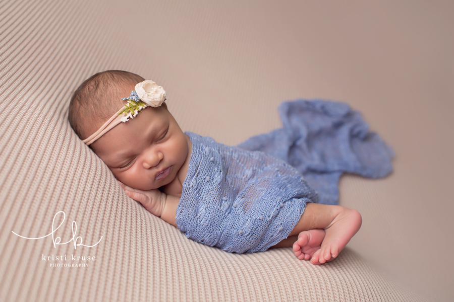 newborn baby girl laying on beige blanket with light blue wrap and matching flower headband