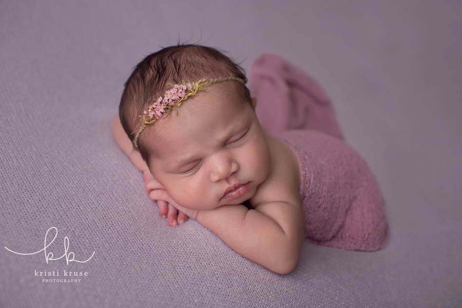 newborn baby girl on lilac blanket with matching wrap and headband