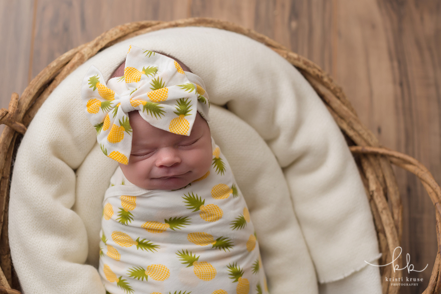 Baby girl wraped in pineapply print swaddle and bow
