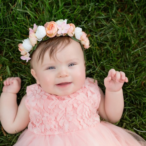 6 month old girl wearing pink dress with pink flower crown laying on grass