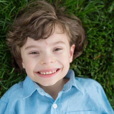 7 year old boy wearing a blue button down shirt lying on grass looking at camera