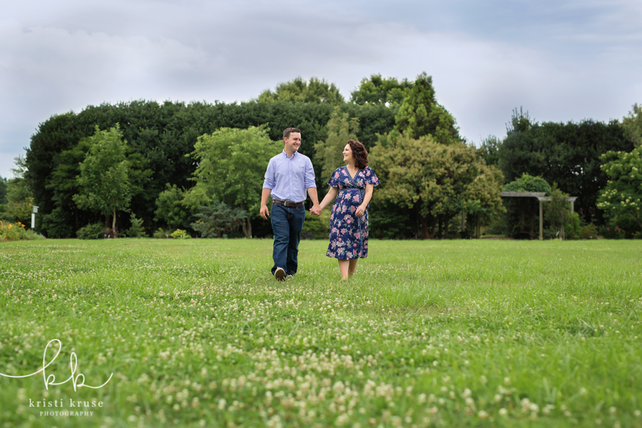 Husband and expectant wife walking across grass field hand in hand