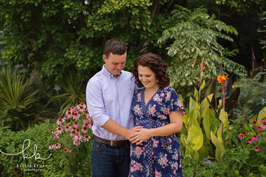 Husband and wife holding hands over pregnant belly